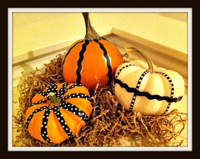 Decorating Mini-Pumpkins with washi tape is a quick and easy craft idea.