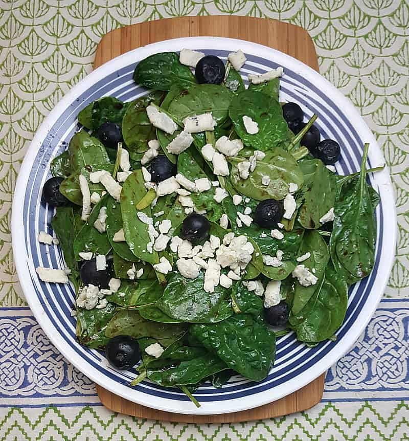 This is a picture of a spinach salad topped with blueberries and blue cheese.