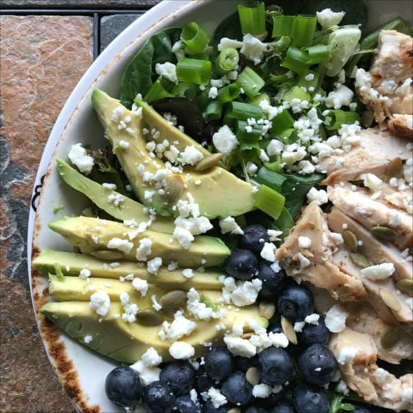 This is a picture of a salad of fresh greens topped with blueberries, avocado, chicken and green onions.