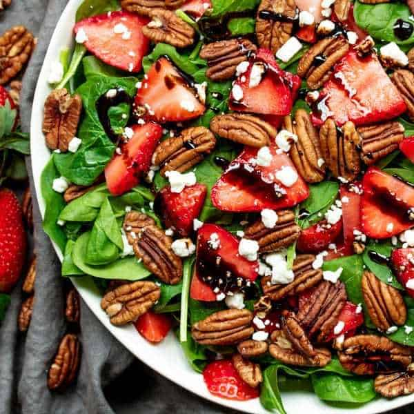 This is a picture a spinach and strawberry salad with pecans.