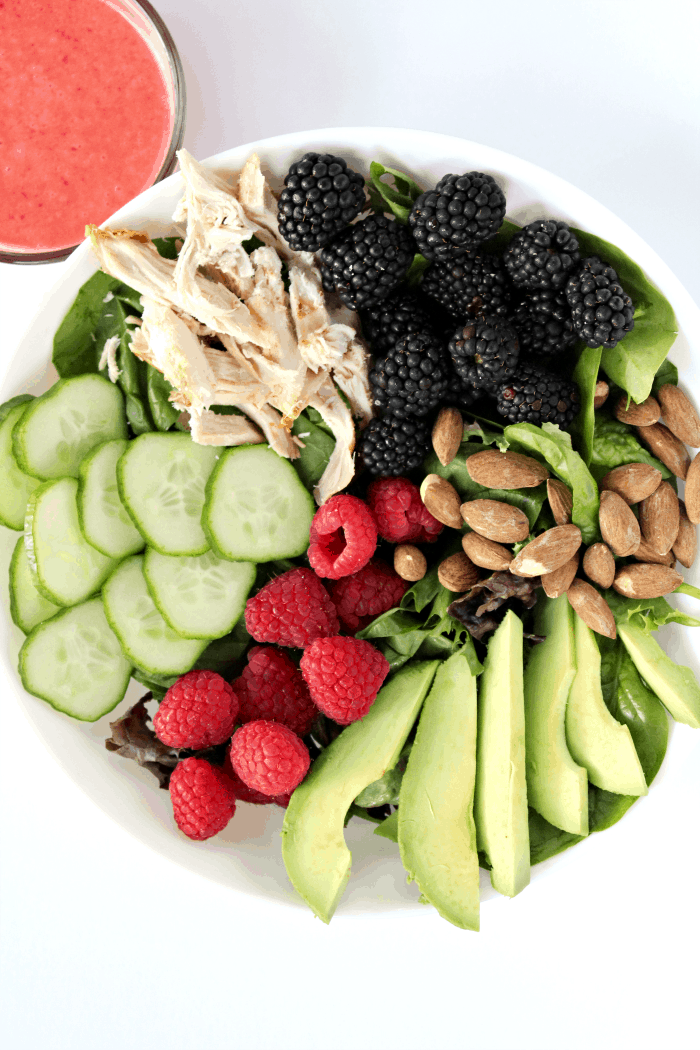 This is a picture of a salad topped with chicken, blackberries, raspberries, almonds and cucumbers.